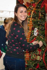 "Liz Newman helping to ""deck the halls"" at the annual office Tree Decorating gathering"